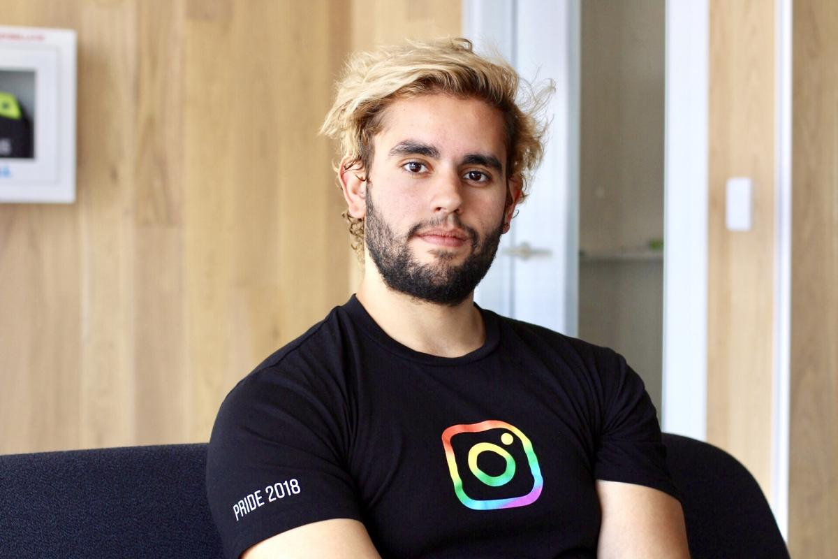 Emilio Joubert smiles into the camera in an office wearing a T-shirt with the Instagram logo on it.